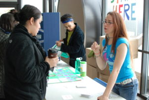 Kyla Newsome (right), president of Wright's Student Environmental Club and a 2015 grad, talks to student Diana Desantiago about Earth Day activities.